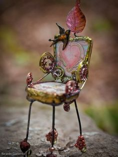 This is a tiny chair made from twisted wire and seed beads for a dollhouse.