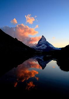 The Matterhorn and late evening clouds are reflected in the tranquil Riffelsee during sunset. Zermatt, Switzerland