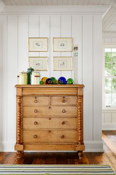 Some furniture is best left unpainted! This untouched pine spindle dresser adds handsome wood tones just off the dining room, while a palette of yellow, green, and indigo keeps the display of outdoor-themed finds—glass floats, camp pails, and antique arrows set in wax—feeling curated, not cluttered.