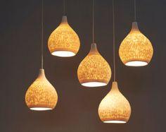 Queste lampade a sospensione moderne sono fatte a mano da lastre di porcellana. La texture delle linee orizzontali è accentuata quando la spia è accesa. I fori permettono alla luce di brillare attraverso. La striscia doro è afixed dopo la prima cottura con oro ceramica speciale 12K lustro che viene poi cotto in un infornamento supplementare e pertanto è resistente al calore.  Questa ciondolo luce crea unatmosfera calda ed elegante.  Questo lampadario unico può essere appeso sopra il tavolo…