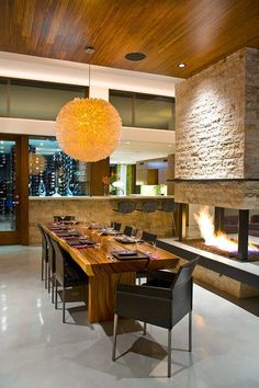 I want the seat next to the fire (or with easiest access to the wine cellar) in this contemporary dining room Contemporary Dining Room Dining Room Fireplace, Cozy Fireplace, Fireplace Design, Fireplace Ideas, Kitchen Fireplaces, Fireplace Update, Fireplace Stone, Wood Slab Dining Table, Dining Table Design