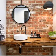 Exposed brick wall, hardwood timber vanity, white round basin, matte black tap and mixer, matte black framed round mirror. Project by - @thewesthomes #taps #interiordesign #bathroom #australia #architecture #bathroomdesign #bathroomcollective Visit our website for more www.bathroomcollective.com.au