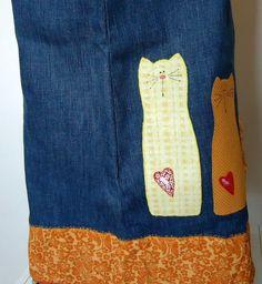 Avental confeccionado em tecido jeans com aplicação de dois gatinhos próximo ao barrado.