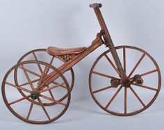"""C-1870 wood trike with cast iron hardware and iron wheel bands retains 95% original salmon paint. 29"""" tall and 40"""" long tricycle also retains black trim paint and pinstripe. Has unusual fully carved seat."""