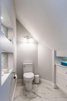 Salle de bain du Lac St-Charles Espace de toilette dans la salle de bain sous le toit en mansarde, fermé par une porte sur rail en bois sur mesure, avec de jolies alcôves avec chevrons en marbre et éclairage intégré.