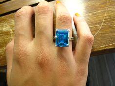 Queen´s Blue von LAAR Vivien  Das perfekt funkelnde Geschenk für romantische Seelen! Diesen handgemachten faszinierenden, rhodinierten und goldplattierten Ring mit einem grossen, dunklen Meerblauen Stein umgibt ein Kranz aus kleinen grünen Steinchen. Mini Steinchen in weiss zieren die obere Hälfte des Rings.