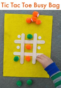 Make a tic tac toe busy bag from craft sticks and pom poms. Genius! Great grab and go activity for kids.