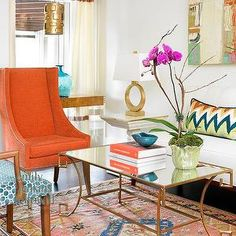 Olive Interiors - living rooms - orange rug, brass lamps, antique brass lamps, orange chairs, orange velvet chairs, orange and blue rug,  Interior