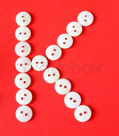 "Image of 'Letter ""K"" from buttons on a red background'"