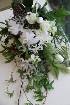 Gorgeous trailing white shower wedding bouquet including Roses, Orchids and Mistletoe