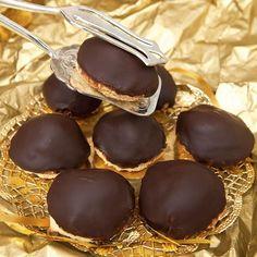 Klassiska chokladbiskvier med len smörkräm under chokladtäcke på segmjuk mandelbotten.