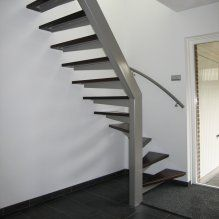 A quarter-landing staircase next to the front door with a doormat and the garage door and on a tile floor.