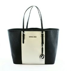 """Michael Kors Black Jet Set Travel Stripe Tote Bag Great carryall purse !    Slightly Used    Details:  - Black and White   - Saffiano leather   - Clasp top closure   -  SIlver MK Charm  - 1 interior zip pocket and 4 open pockets  - Key FOB -  11 1/2"""" H x 19"""" L x  6 1/2"""" D  Handle straps:  8""""   - Original tags and dust bag are NOT included    * All Images are of the actual product. 100% Authentic Michael Kors*  ** Exterior has minor dents on the bottom  and the lower back hardly noticeable…"""