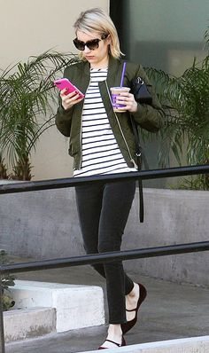 Emma Roberts wears a striped tee, black skinny jeans, black flats, and a green bomber jacket.