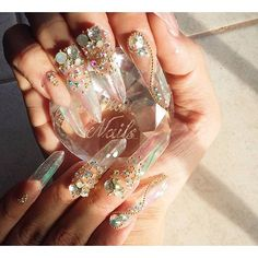 Prism edge nails with iridescent film strips covered in a gel, and topped with crystals.