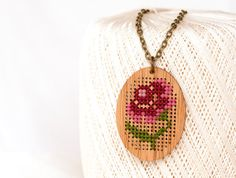 A traditional cross stitch pattern gets a modern twist in this unique cross stitch pendant. The kit provides everything you need to make your own necklace. It's a DIY project easy enough for beginners.  Each pendant, made from lightweight, eco-friendly bamboo, measures approximately 1-3/4 inches high and 1-1/4 inches wide, and has a stitching area of 19x13 stitches at the widest points.