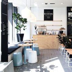 Modernes Café mit weiß getünchten Böden, schwarzen Akzenten und Pastelltönen