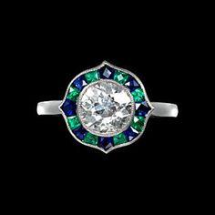Brilliant cut diamond ring with sapphire and emerald surround in platinum. Art Deco or Art Deco style.