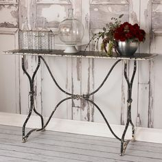 "White and Black Distressed Metal Table Classic curves and vintage motifs add to the distressed antique look of this metal console table. The black painted finish is chipped to look old and worn showing a white finish on the edges and scuffed on the legs. A perfect size console table for foyers, kitchens and living rooms. Some assembly required. (33""Hx55""Wx17""D)"