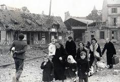Caen, 6 juin 1944. Les familles sinistrées fuient le centre  ville en début d'après-midi. Ici, place Courtonne - Boulevard des Alliés.