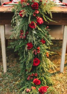 You need to see these 10 ideas for a Winter wonderland wedding! Gorgeous red roses cover lush green garland creating a wow-worthy tabletop.
