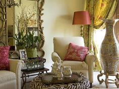 An inviting sitting area in a master bedroom suite was created using cream upholstered reclining chairs, a chocolate zebra-print skirted ottoman, antique wool area rug and tiered granite-topped side tables.