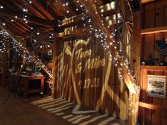 Love the names of the bride and groom with the date projected on the wall in this barn / rustic wedding theme!