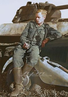 A Wehrmacht Heer member poses on the fender of a Sd.Kfz. 2 Mercedes-Benz Type 170 VK with a burned out Soviet T-34-76 tank in the background - Summer 1941 He is sporting the fashionable undercut (hairstyle), a version of this haircut was long on top but shaved at the back and sides, being popular among Wehrmacht officers.