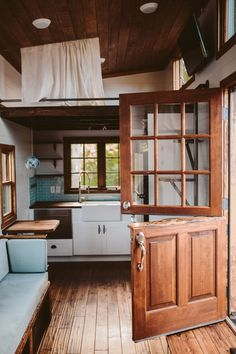 Dutch door, built in couch with storage that pulls out to twin bed, guest loft with privacy curtain. The Mayflower by Wind River Tiny Homes.