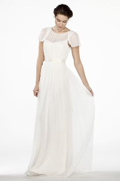 """A sheer illusion dress with a low plunge back and flutter sleeves that drape and frame perfectly around the shoulders. This simple, modern wedding dress showcases the collarbones and neckline of the bride beautifully. • Can be accessorized with many sashes and belts from our accessory page. Made of 100% silk: • Top layer: Off white silk chiffon. • Lining: Cream silk charmeuse. • Comes with 2"""" wide cream silk charmeuse sash. • The dress has a low back neck drop. • Should be worn with a p..."""