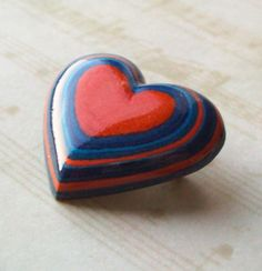 Layered paper heart brooch.