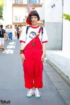 Sato (aka SATO@310) is a 17-year-old student – with a cropped bob hairstyle and a red backwards cap – spotted in Harajuku. Sato's t-shirt is from the Harajuku resale shop Panama Boy, worn with red overalls that are half closed and rolled up. Her sneakers are Adidas and she is also wearing a sneaker print backpack, a star pin and a flames-print sports cuff. (Tokyo Fashion, 2014)