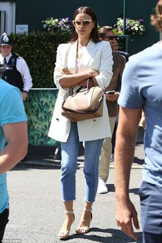 Prefers tennis to football? A stern-looking Irina Shayk wore cut-off denim and a cream jac...