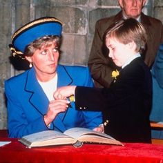 March 1, 1991: Princess Diana with Prince William at the St. David's Day service signing the register at Llandaff Cathedral in Cardiff, Wales. This is Prince William's first public engagement.