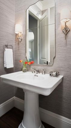 Gray powder room features walls clad in gray sisal wallpaper lined with a curved chrome mirror illuminated by Etoile Sconces placed above a pedestal sink.