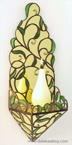 Stained glass candle sconce. This sconce is made with antique golden colored mirror, spectrum glass for the leaves and wire overlays.