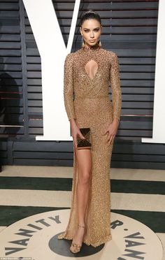 Golden girl: Adriana Lima looked incredible in a tight gold gown with a keyhole...