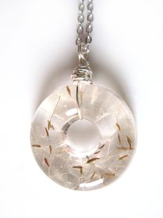 This listing is for a lovely pendant of several fluffy dandelion seeds encased in jewelers grade resin. The pendant is a donut shape. I have wire wrapped a silver tone wire through a hole at the top that acts as a bail. This would be a wonderful gift for Mothers Day or any day! It is a fun shape and substantial size for a wonderful statement pendant! Please note that the back of the pendant is flat and not rounded like the front of the pendant.   The pendant measures about 1 1/2 round ...