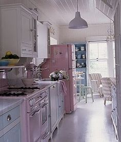 I mean, WOW! This is pretty much my dream kitchen, from the Merritt & O'Keefe vintage stove to the Pink Big Chill fridge. My favorite house has a galley kitchen layout and I am liking the wainscotting and the white cabinets and the pale blue accents. I love marble countertops but I have heard they stain...