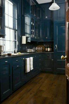 Floor to Ceiling Cabinetry. Dark Blue Kitchen. some glassed cabinet doors. towel bar/ drawer pulls. brushed silver old fashioned farmhouse drawer pulls. hardwood floor.