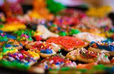 Cookies de différentes couleurs, saupoudrés de vermicelles arc-en-ciel.