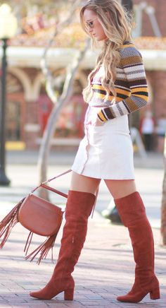 Retro casual fall outfit styled with striped turtleneck, white button up skirt, rust over the knee boots, and fringe crossbody bag