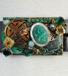 Vintage buckle by designer Chelsey Loren is crafted from one of a kind antique and vintage jewelry pieces. This buckle is adorned with 40s celluloid jade floral layered under a copper Asian circle, 40's scarab pieces, lucky chinese dragons, a victorian engraved oval and 40's rhinestone filigree circle. Shown on a brown leather strap. Enjoy your fashionable piece of wearable art!