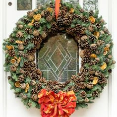 Extra large Christmas wreath with dried orange slices and pinecones. Available to buy online from London based florists Okishima & Simmonds. www.okishimasimmonds.com