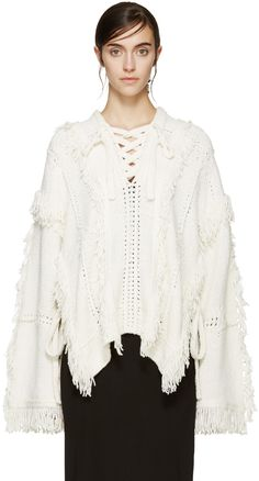 Long sleeve wool-blend poncho in ivory. Crochet panelling and fringed trim throughout. V-neck collar with tonal lace-up closure.  Dropped shoulders. Extended vent at sides with self-tie fastening. Tonal stitching.