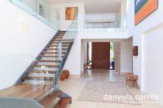 Entrada casa de praia, porta pivotante vermelha, piso porcelanato, parede de pedras, aparador.  Escada com estrutura metálica e madeira, corrimão e guarda corpo em vidro. Decoração com quadros. Arquiteta Danyela Corrêa