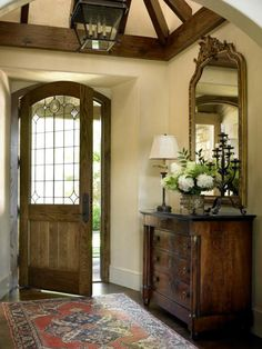 Very English feel to this foyer....love the chest, mirror, rug, door, vaulted ceiling..... (Francie Hargrove)
