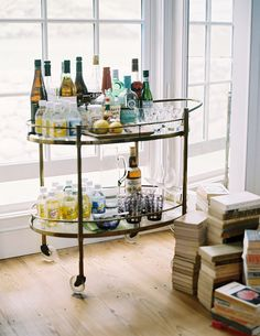 A vintage brass bar cart of spirits, mixers, and glassware as featured on Lonny.com.