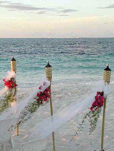 IDEAS DECORACIONES BODA AIRE LIBRE. Antorchas de bambú decoradas con tul y flores