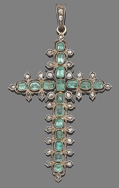 An emerald and diamond pendant  The cross of openwork design set throughout with cut-cornered step-cut emeralds, with rose-cut diamond highlights, length 7.6cm.